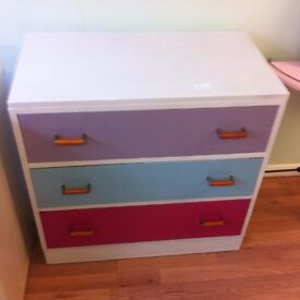 Drawer chest with three different colored drawers.