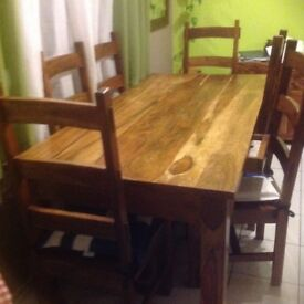 Solid wood dining table with six chairs and a cupboard