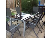 Black glass outdoor table with 6 free chairs.