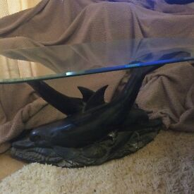 Glasstop coffee table with dolphin design base