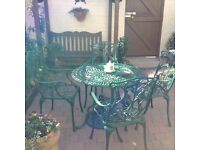 Garden table and four chairs. Cast iron painted green. Beige cushions . Great condition