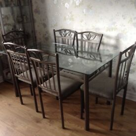 Glass dinning table complete with 8 chairs