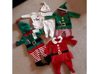 Bundle of newborn baby snowsuits and christmas wear.