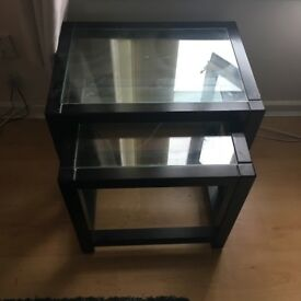 Black wooden nesting tables with glass tops