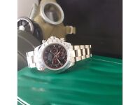 Silver Rolex Daytona with black face, red sub dials, silver casing and all silver oyster bracele.