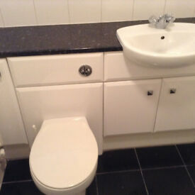 Gloss white vanity sink unit with matching toilet unit.