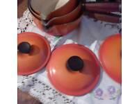 3 cruset saucepans in volcanic orange