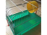 Hamster Cage including wheel, food bowl, log tunnel and hamster house.