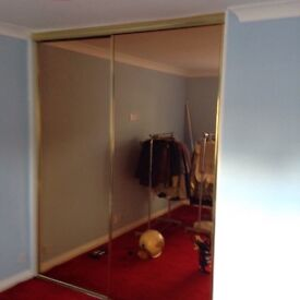 A PAIR OF MIRRORED SLIDING WARDROBE DOORS