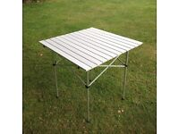 Weatherproof camping/patio table in slatted alumnium complete with carry bag excellent condition