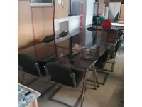 Black glass boardroom table with 8 black chairs
