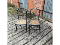 A pair of Victorian ebonised bergere chairs