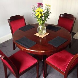 Round dark brown table with comfy four chairs.