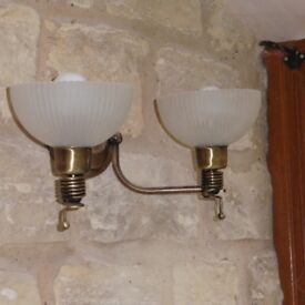 A pair of double antique bronze wall lights