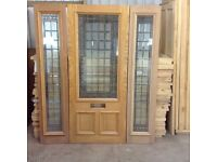 Quality hardwood front door with side panels.