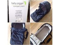 Baby Jogger carry cot with single and double pram adapters.