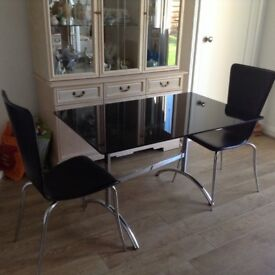 Black glass and chrome table and two leather effect chairs