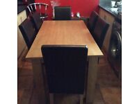 Light oak table with slight mark(see photo) and 6 dark brown leather effect chairs £90.00