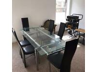 Glass table and 6 black chairs £200