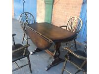 Ercol Extending Old Colonial circular dining Table and Four Carver chairs.