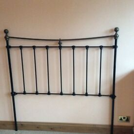 Black metal bedhead with brass finials
