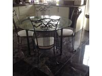 Wrought Iron glass top circular table + 6 chairs upholstered chairs