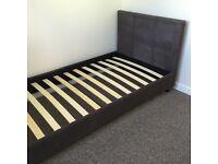 Unused single slatted bed frame with headboard brown upholstered frame