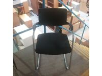 Black cushioned stacking chair with grey metal legs