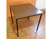 Formica topped square stacking table with metal legs.