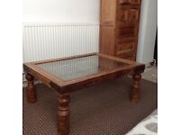 Beautiful wooden and wrought iron coffee table with glass top.