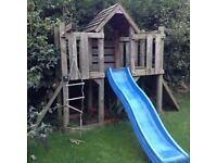 Wooden play equipment with climbing wall, slide and rope ladder
