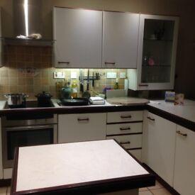 White Paula Rosa Satin Finished Kitchen Units with Mahogny Handles and Trim and Neff Appliances