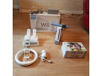 Boxed, white Nintendo wii. 2 remote controllers + charging dock + steering wheel + 6 quality games