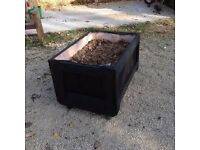 Black planter boxes with wheels