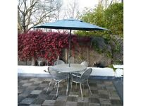 large garden or patio metal table with chairs and parasol can deliver