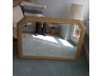 Oblong mirror set in a stress gold frame