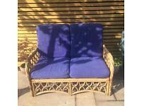 2-seater cane outdoor seat with blue cushions