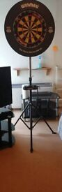 Dart board, rubber surround, travel stand and 3 sets of darts