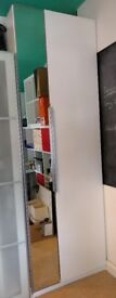 Tall white IKEA wardrobe with slim mirror door. Filled with baskets and shelves