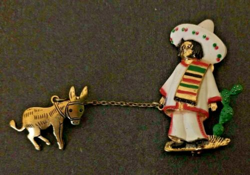 1940S GOLDTONE META ENAMELWARE MEXICAN MAN WITH SOMBRERO PULLING DONKEY ON CHAIN