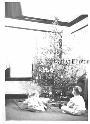FOUND B&W PHOTO G_0100 BABY AND BOY IN FRONT OF CHRISTMAS TREE TRAIN SET