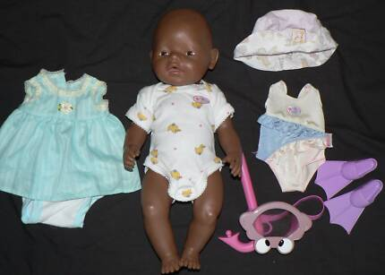 Ethnic Baby Born doll with a few outfits.