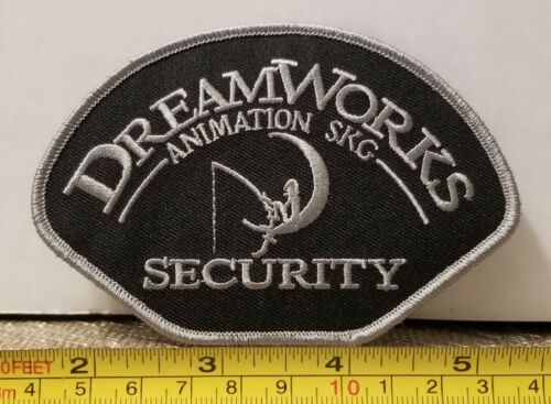 "Dreamworks Animation Security Shoulder Patch.  4.75""×3.25"".  Grey on Black"