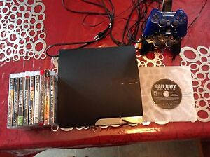 PlayStation 3 with controllers and controller charger with games