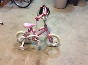 Small child's bike with training wheels and helmet