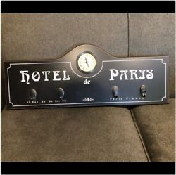 Black Wall Clock With Hooks and White Writing - Hotel de Paris