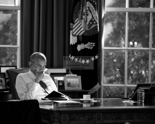 BARACK OBAMA REVIEWS BRIEFING MATERIALS IN THE OVAL OFFICE - 8X10 PHOTO (OP-189)