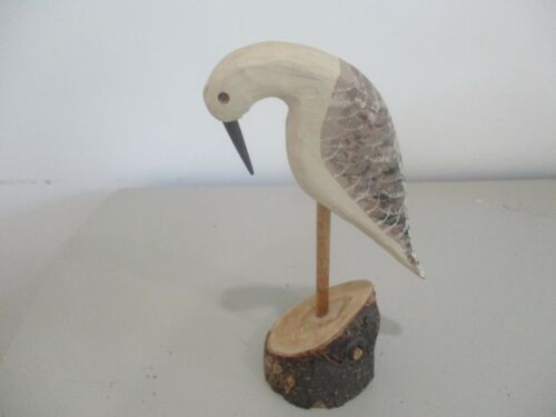 Small carved bird on a perch.