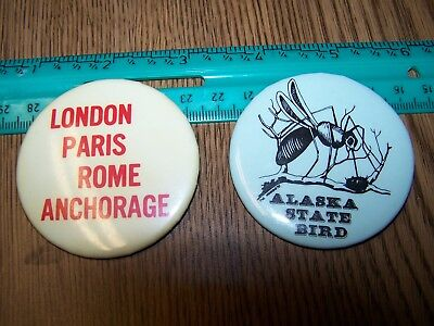 "2 Alaska tourist buttons, State bird & international cities. 2.25"". Very fine."