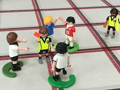 Seven Playmobil football figures including referee and linesmen